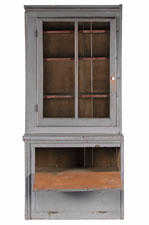 NARROW, MAKE-DO PENNSYLVANIA CUPBOARD IN OLD GREY PAINT OVER AN EARLIER RED, WITH A GLAZED DOOR AND TWO UNUSUAL DROP-DOWN DOORS, CA 1890