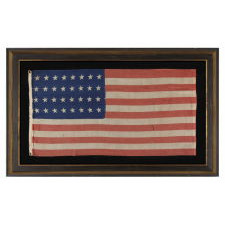 32 STAR ANTIQUE AMERICAN FLAG, REPRESENTING MINNESOTA STATEHOOD, 1858-59, IN A STYLE KNOWN TO HAVE SEEN MILITARY SERVICE DURING THE FORTHCOMING CIVIL WAR (1861-65) AND BEARING THE SIGNATURE OF A SOLDIER WHO FOUGHT WITH THE 15TH MICHIGAN INFANTRY, POSSIBLY MADE BY THE ANNIN COMPANY IN NEW YORK CITY