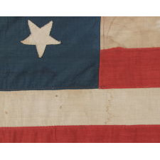 13 HAND-SEWN STARS ARRANGED IN A 3-2-3-2-3 PATTERN, WITH VARYING VERTICAL ORIENTATION, ON A HOMEMADE ANTIQUE AMERICAN FLAG DATING TO THE ERA OF THE 1876 CENTENNIAL OF AMERICAN INDEPENDENCE