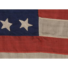 32 STARS ON AN ANTIQUE AMERICAN FLAG WITH ITS CANTON RESTING ON THE WAR STRIPE, MADE IN THE PERIOD WHEN MINNESOTA JOINED THE UNION AS THE 32nd STATE; A VERY RARE STAR COUNT, OFFICIAL FOR JUST ONE YEAR, AND ACCURATE FOR JUST NINE MONTHS, 1858-59