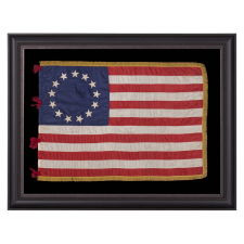 BEAUTIFULLY GRAPHIC AND HIGHLY UNORDINARY 13 STAR FLAG IN THE BETSY ROSS PATTERN, A MADE OF FINE SILK WITH SILK FRINGE AND TIES, IN A TINY SIZE AMONG ITS COUNTERPARTS CA 1895-1926