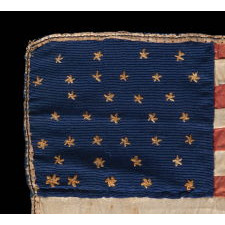 34 NEEDLEWORK STARS ON A TINY, HAND-SEWN, SILK AMERICAN FLAG, AT ONE TIME SEWN INTO A QUILT MADE DURING THE OPENING YEARS OF THE CIVIL WAR, 1861-63, REFLECTS KANSAS STATEHOOD